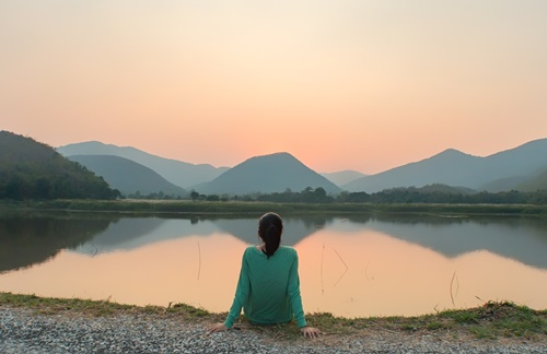 Woman relaxing and looking at lake at sunset